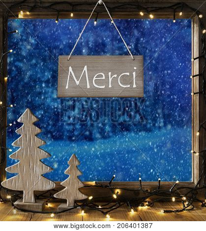 Sign With French Text Merci Means Thank You. Window Frame With Winter Landscape With Snow. View To Snowy Trees Outside With Snowflakes. Christmas Tree And Fairy Lights.