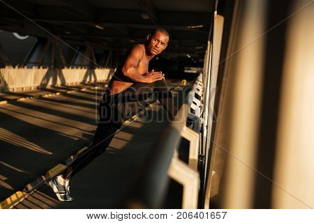 Full length portrait of a young concentrated half naked african sportsman doing stretching exercises while leaning on a handrail and looking away indoors