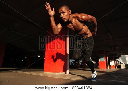 Full length portrait of a concentrated motivated half naked african sportsman starting to run indoors
