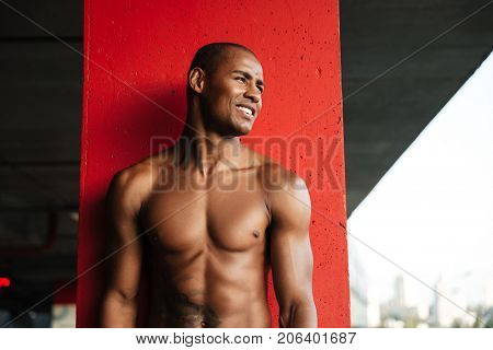 Portrait of a young smiling half naked african sportsman looking away while standing indoors