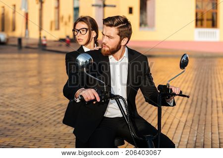 Careful business couple rides on modern motorbike in park and looking away