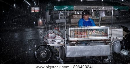BANGKOK THAILAND - AUGUST 08: An unidentified street food vendor with a modified motorcycle side-cart continues to do business in a rainstorm on August 08 2017 in Bangkok.