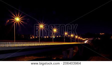 Night motorway illuminated by bright beams of lanterns