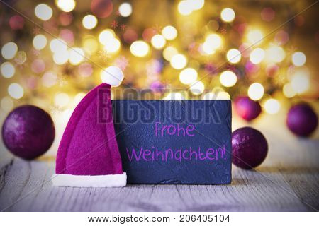 Plate With German Text Frohe Weihnachten Means Merry Christmas. Purple Christmas Ball Ornaments And Santa Claus Hat. Wooden Background With Lights