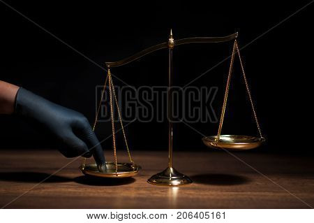 Hand with black glove pushing on scale of justice in dark room with black background. Concept of injustice espionage partiality law.