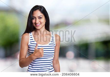 Beautiful turkish woman in a summer shirt showing thumb up