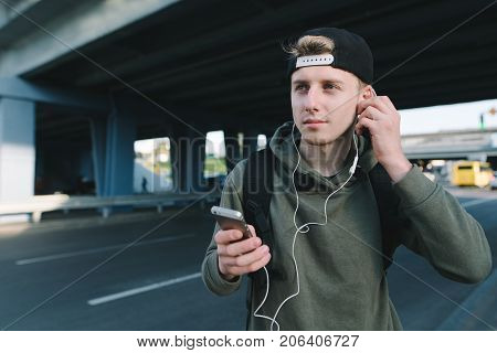 A stylish young man in a cap fixes the headphones in his ears and holds the phone in the back of urban architecture.