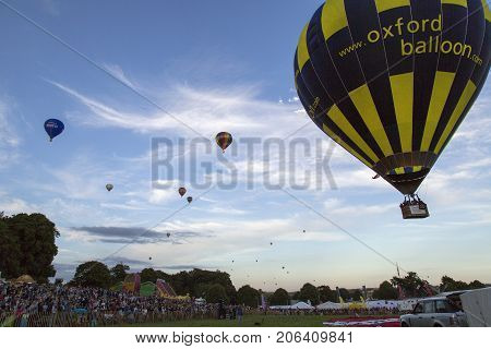 Bristol, UK: August 13, 2016: Flying the balloons at the Bristol International Balloon Fiesta. Spectators surround the main attraction as all the balloons lift off for the evening Mass Ascent.