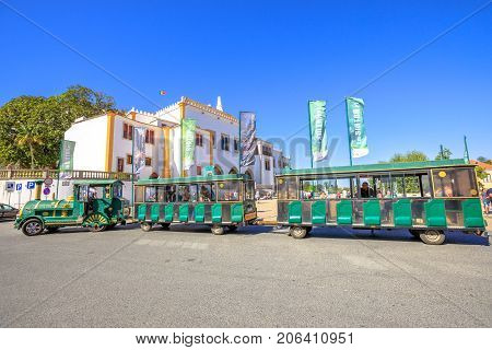 Lisbon, Portugal - August 8, 2017: Green Tourist Train in Amelia Square, in front of National Palace of Sintra, in Portuguese Palacio Nacional de Sintra, in urban historic center. Unesco Heritage Site