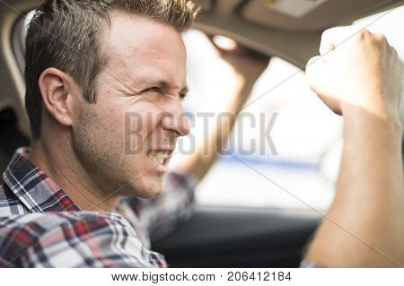 An Irritated young man driving a car