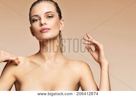 Gorgeous young woman enjoying her perfect skin. Portrait of woman with beautiful makeup on beige background. Beauty & Skin care concept