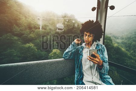 Charming young black girl with curly afro hair in jeans jacket sitting inside of cable railway cabin and making selfie on her smartphone rainy mountain landscape outside Rosa Khutor resort Russia