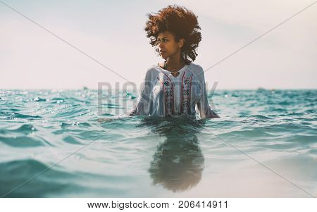 Attractive young black curly girl in traditional African chemise is standing up to the waist in ocean water and looking aside strong reflection in the bottom ripples on water surface