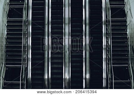 Top view of contemporary glass and chrome escalator line of four tracks with two stairways on both sides in airport terminal deport or modern mall building strong metallic specular