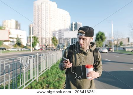 A young man with headphones in the ears and coffee in the yoke strolls around the city and uses the phone. Lifestyle and people concept. Lifestyle and people concept.