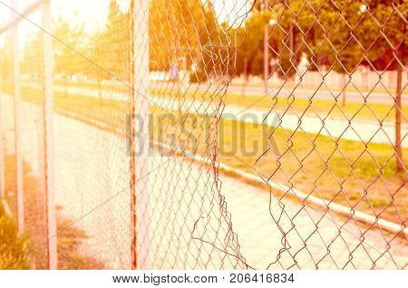 Chain link wire fence with hole parallel with the street and with sunlight