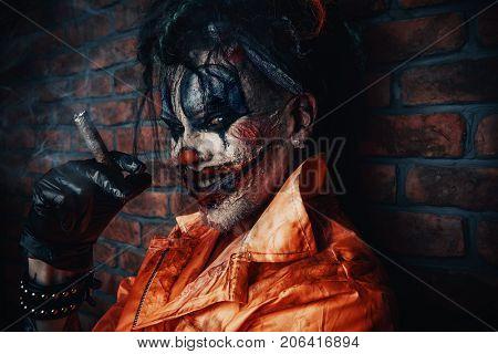 Halloween. Portrait of a bloodthirsty clown man over dark brick wall. Male zombie clown. Horror, thriller film.