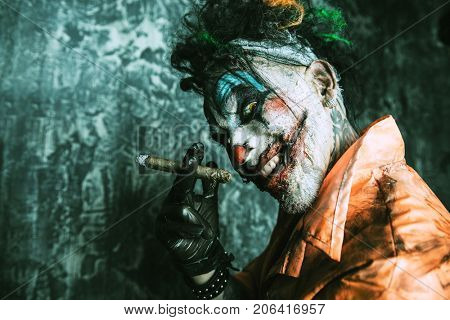 Halloween. Portrait of a disgusting clown man stained in blood over dark background. Male zombie clown. Horror, thriller film.