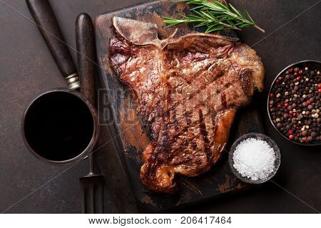 Grilled T-bone steak and red wine glass on stone table. Top view