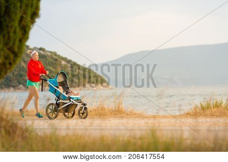 Mother with child in stroller running and enjoying motherhood at sunset and mountains landscape. Jogging or power walking woman with pram at sunset. Beautiful inspirational mountains landscape.