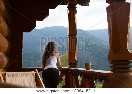 Woman leaning on wooden handrail and enjoys beautiful mountain scenic. Young female on terrace leaning on handrail with a cup of tea or coffee