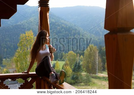 Woman leaning on wooden handrail and enjoys beautiful mountain scenic. Young female on terrace sitting on handrail with a cup of tea or coffee