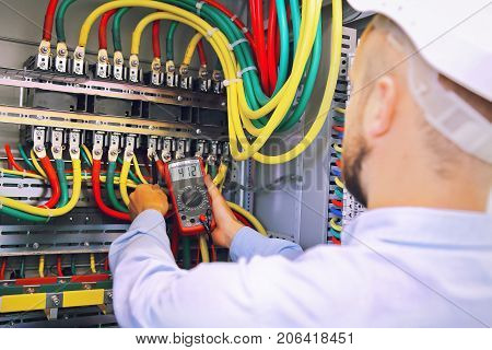 Electrician engineer measures voltage with multimeter in high voltage cabinet.