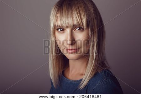 Closeup portrait of beautiful young middle age blonde Caucasian woman looking in camera. Girl female with long blonde hair bob studio beauty shot.