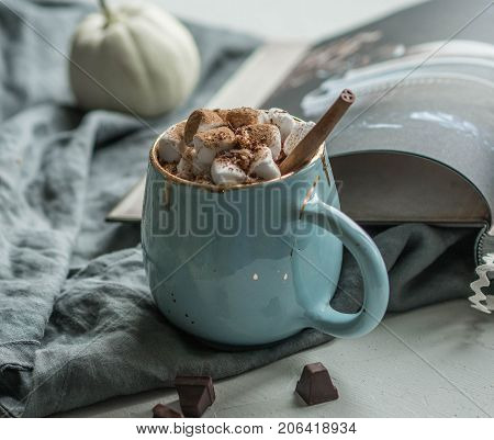 Hot chocolate with marshmallow in a blue mug with a cinnamon stick. an open book next door, one white pumpkin and several pieces of chocolate on a gray background