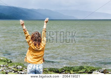 Back Of Young Woman Looking At Stormy Dark Green Ocean Or River With Curly Hair Blowing In The Wind