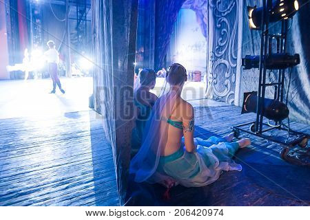 ballet, illumination, backstage concept. in the light of spotlights adorable ballerinas wearing turquoise costumes of east beauties sitting on little pillows and waiting in the wings for their cue