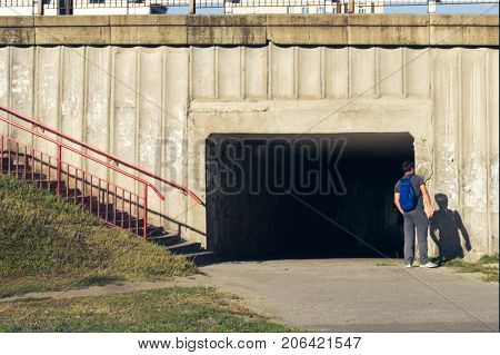 A man waiting for someone standing near an underground passage
