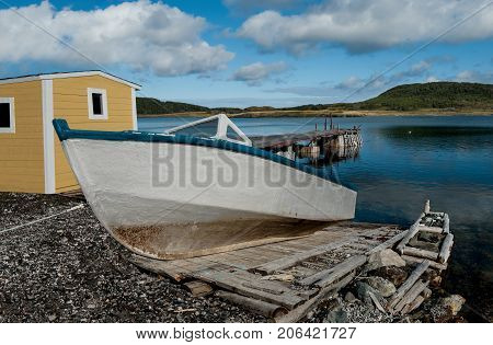 Boat on a Wooden Ramp:  A weathered fishing boat sits on a handmade ramp for launching into a bay on the west coast of Newfoundland.