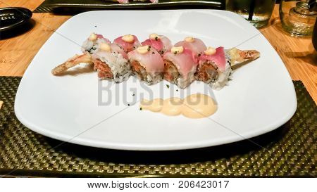 A delightful sushi dinner while out with friends. Has shrimp tempura & spicy tuna inside and tuna and salmon on top.