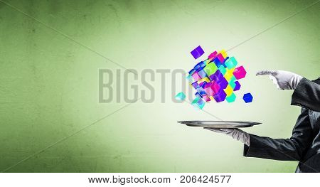 Cropped image of waiter's hand in white glove presenting multiple cubes on metal tray with green background. 3D rendering.