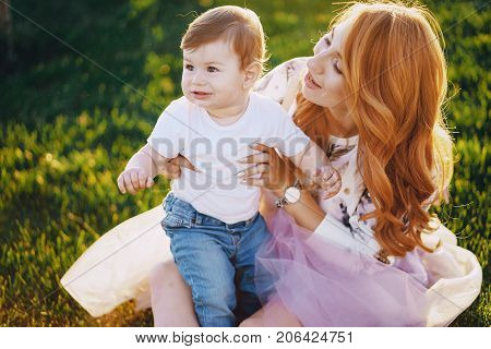 Beautiful red-haired woman with her wonderful son on a summer park