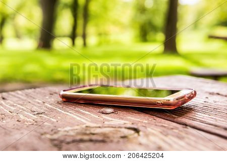 Macro closeup of lost generic light pink rose gold smartphone phone left forgotten in plastic clear case lying on table in outside summer park