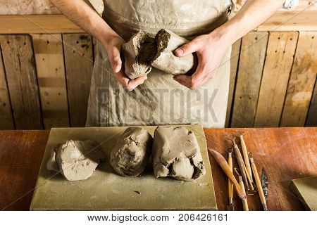 pottery, clay, ceramics art concept - top view on hands of young master holding the large pieces of fireclay, male dressed in an apron, a ceramist with raw materials on table with sculpting tools set