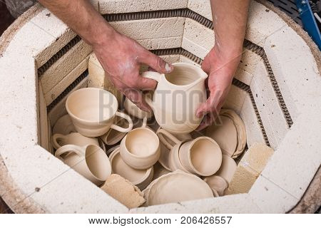 pottery, workshop, ceramics art concept - close-up on electric oven for roasting of unbaked clay products, male hands putting the jug into the kiln, some unfinished cups and utensil