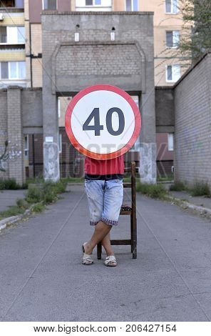 Road sign speed ​​limiter 40 kilometers legs at the sign a sign on the road a round sign a road sign travel to the residential area speed ​​warning sign limiting speed.