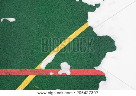 A close-up is a specialized outdoor sports ground covering a rubber crumb of green color with marked lines for playing sports. Covered with snow. The concept of sports in winter. View from above