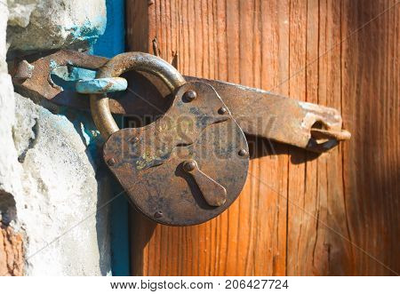 old padlock hanging on the door.old wooden door locked