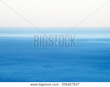 a sailboat with a white sail far out to sea