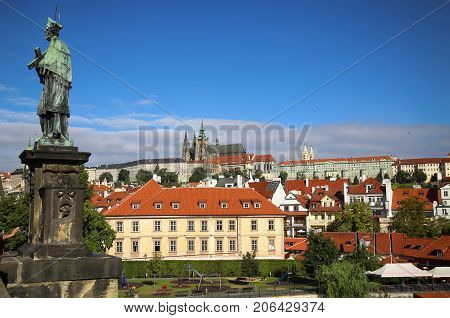 Panoramic view on St. Vitus Cathedral from Charles Bridge with statues of St. John of Nepomuk in Prague Czech Republic