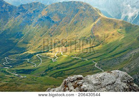 Dolomites mountains with a winding road visible on a misty day