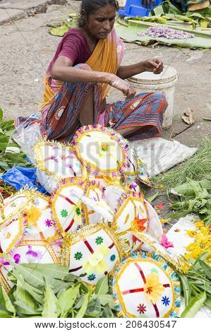 PONDICHERY PUDUCHERY INDIA - AUGUST 26 2017. Vendor selling fresh flowers vegetables fruits and umbrella for devotees to bless Hindu god Ganesh at local market on the first day of Ganesh Chaturathi festival