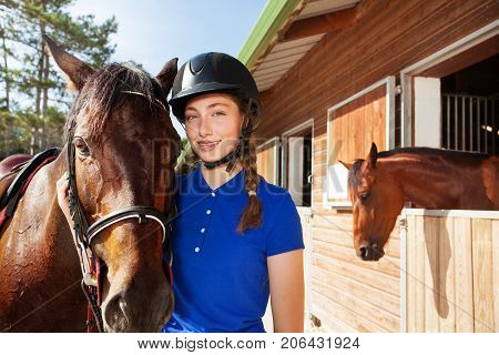Beautiful young woman wearing riding helmet standing outside a box stall with her brown horse
