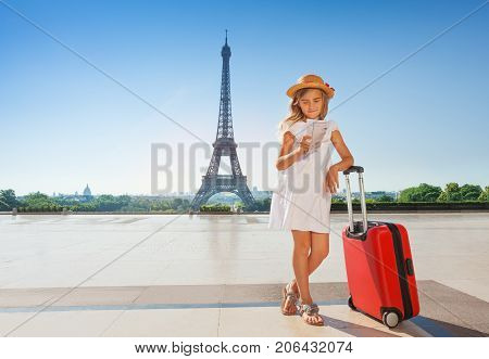 Portrait of elegant preteen girl standing with suitcase against the Eiffel Tower and reading a guide Map from public domain published before 1923 source tourvideos.com