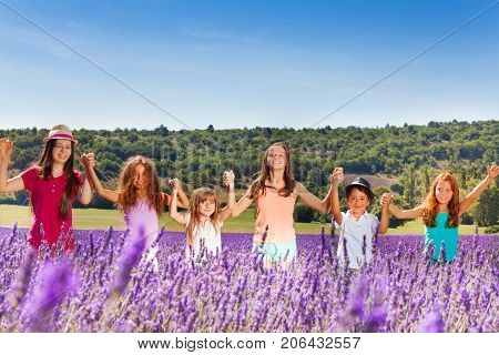 Happy age-diverse children standing together in lavender field, holding their hands up in summertime