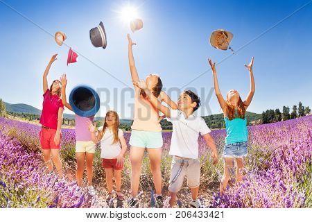 Group of age-diverse kids standing in lavender field and tossing up their hats over blue sky in summer